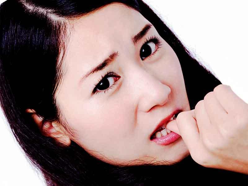 嫉妬で爪を噛んでる女性