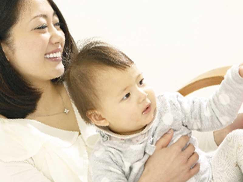 椅子に座っているお母さんが赤ちゃんを抱っこしてる