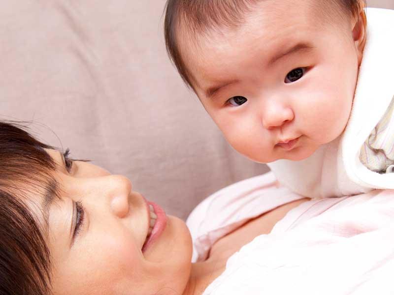 横になっているお母さんの上に赤ちゃんがいる