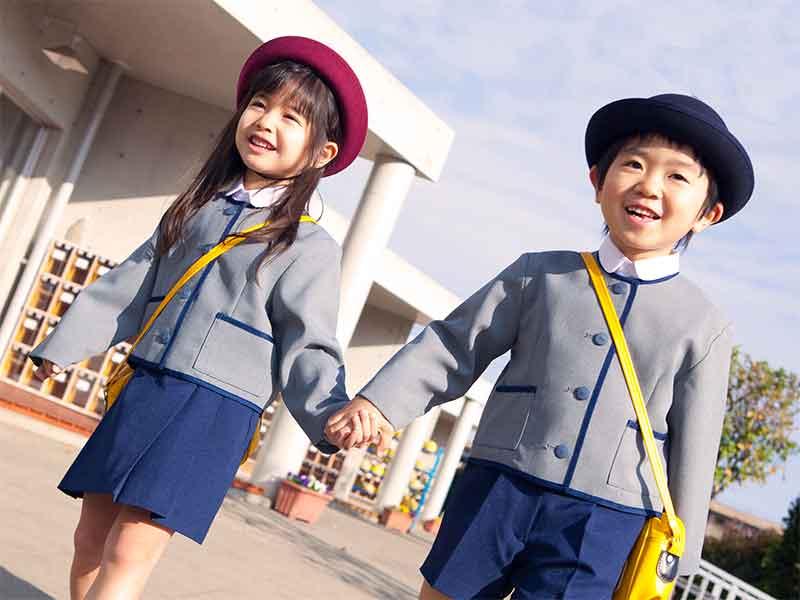手を繋いで幼稚園に登園してる女の子と男の子