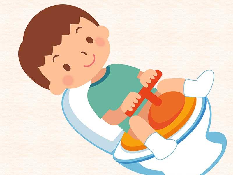 子供用の補助便座付きのトイレに座ってる子供