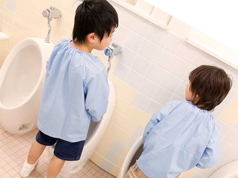 幼稚園のトイレでおしっこをしている男の子