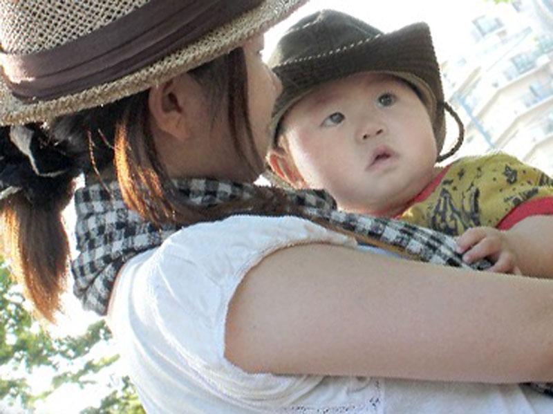 お母さんに抱っこされて散歩している赤ちゃん