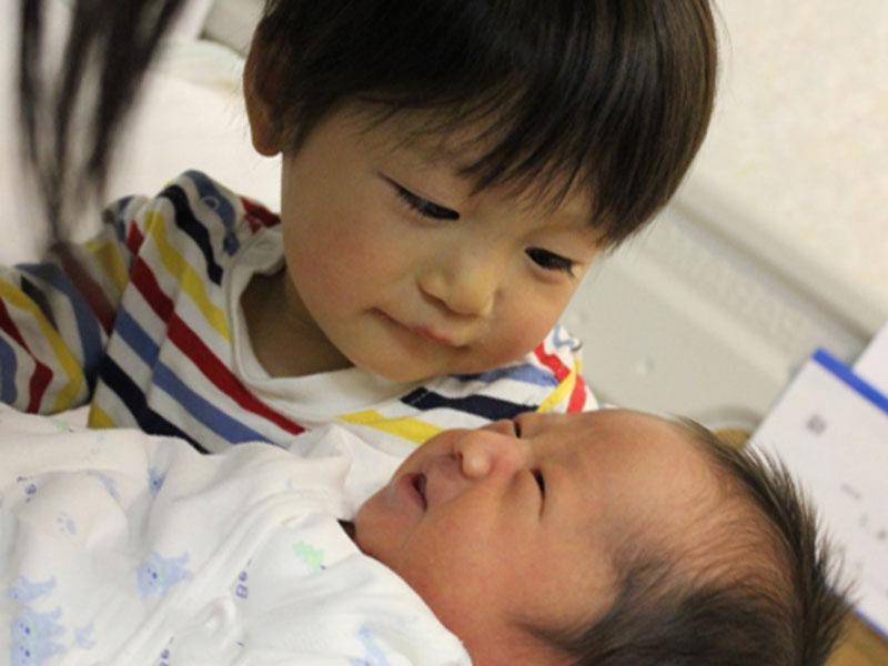 お兄ちゃんが生まれたばかりの赤ちゃん兄弟を見ている