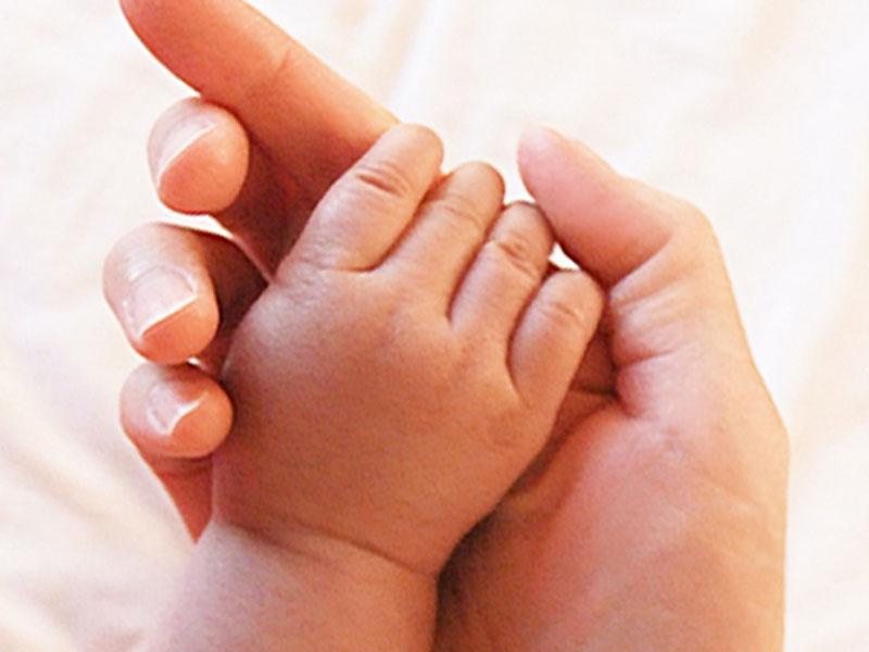 赤ちゃんの手を握っている