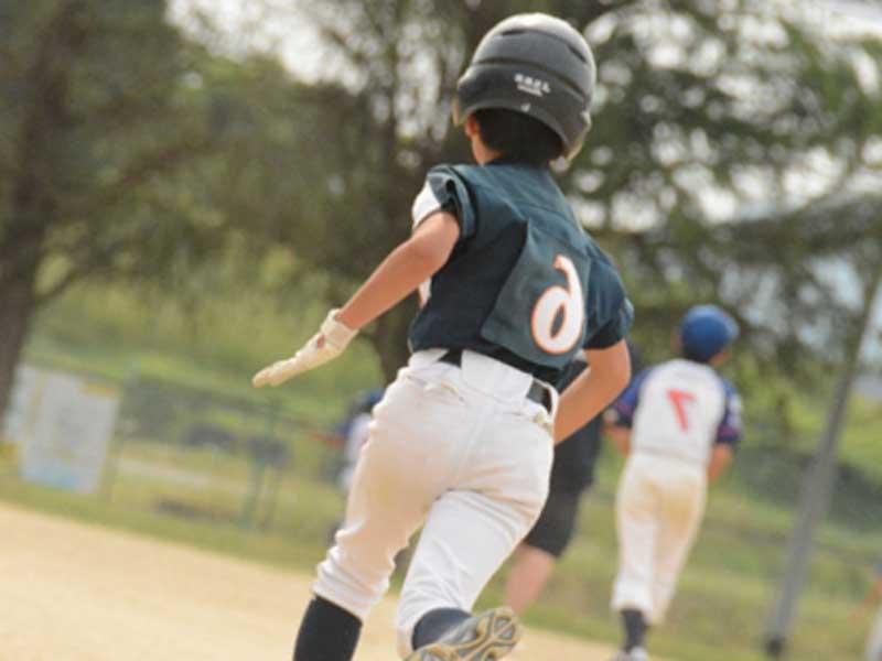 走っている野球少年