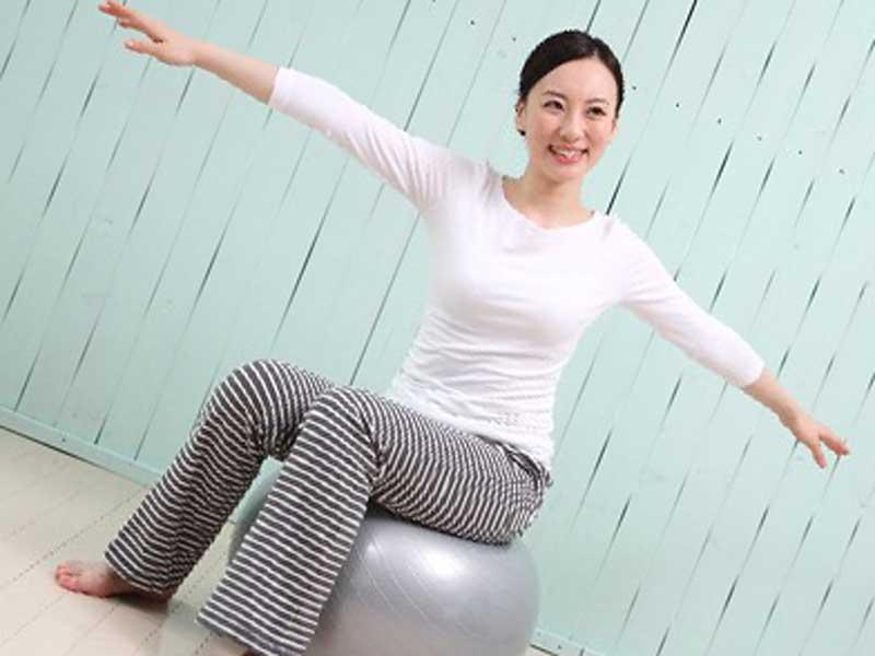 バランスボールに座っている女性