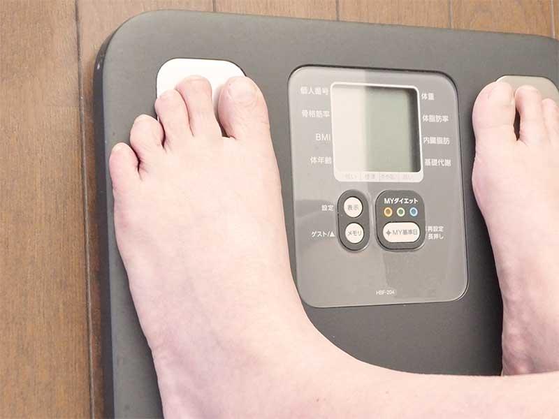 体重計に乗ってる女性の足元