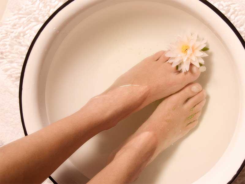 足湯で身体を温めてる女性の足元