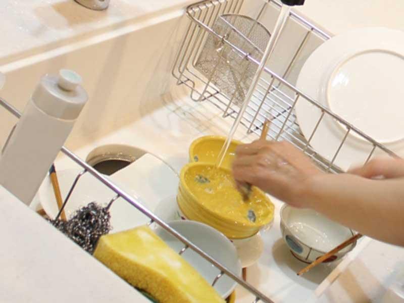 台所でお椀を洗っている