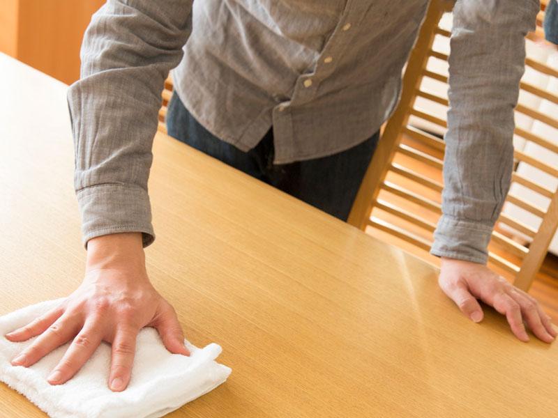 テーブルを拭いている男性