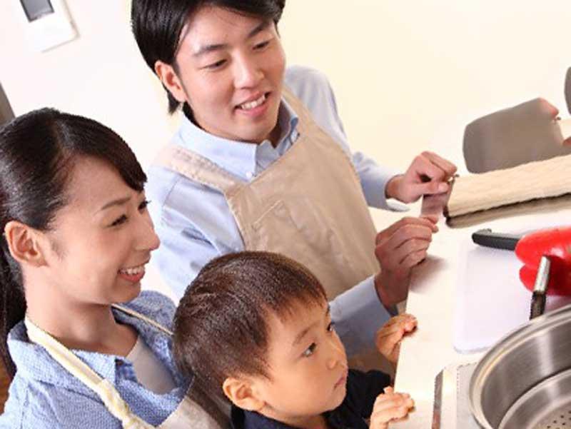 台所にいる子供とエプロンをしているお母さんとお父さん