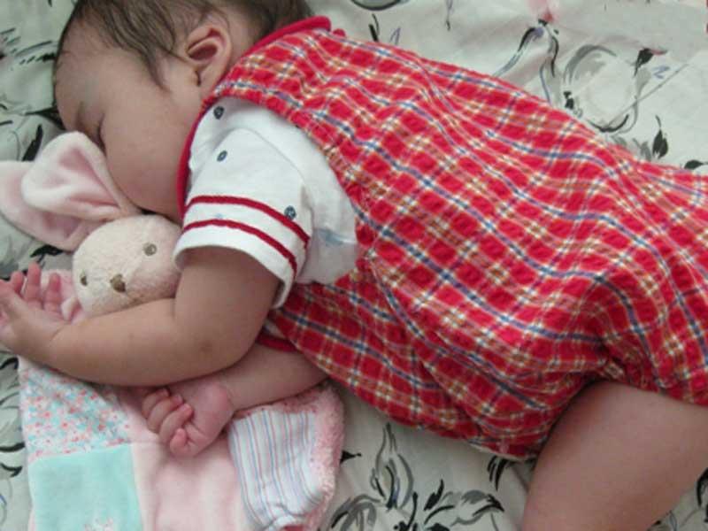 ぬいぐるみを抱っこして寝る赤ちゃん