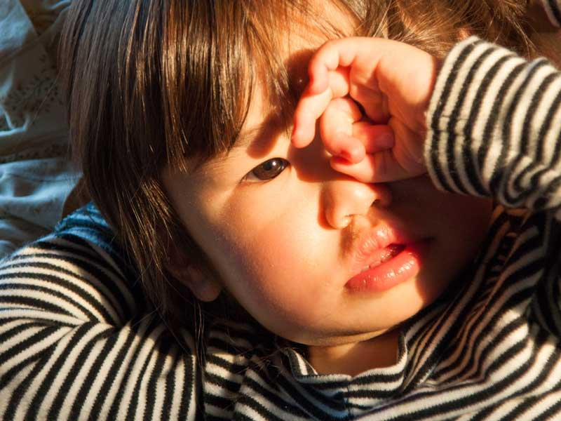目を掻いている赤ちゃん