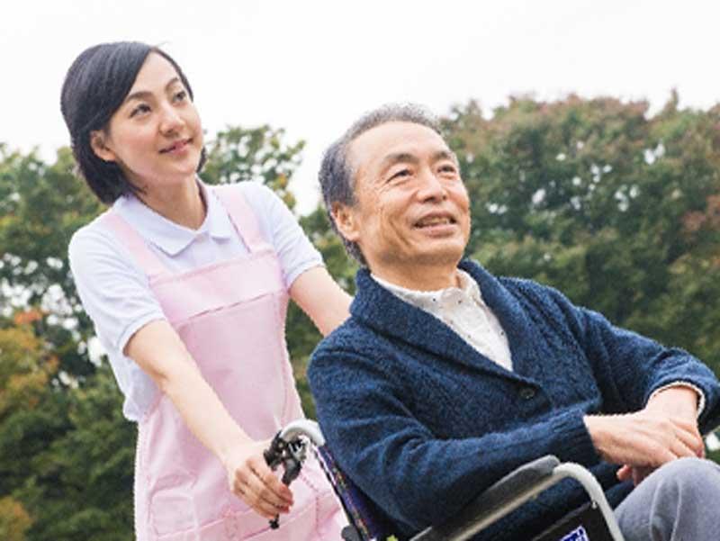 車椅子を押している介護職員の女性
