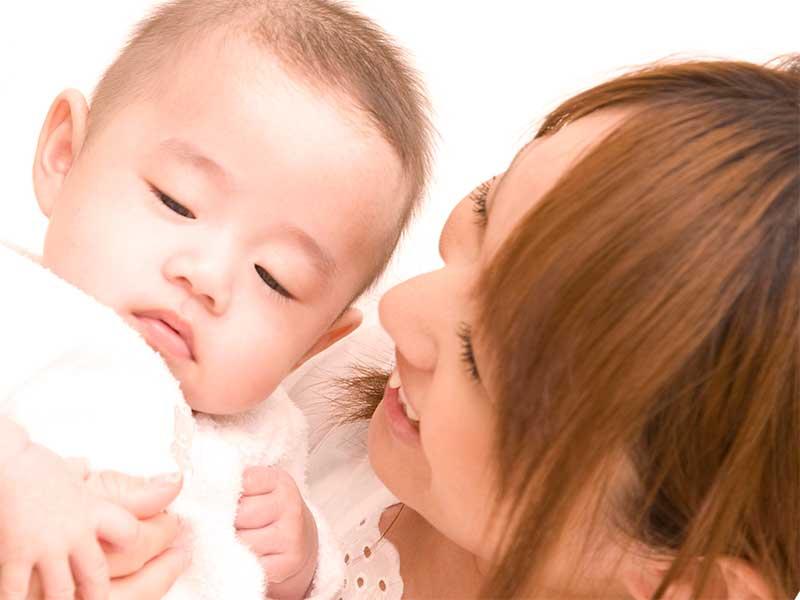 抱っこしてる赤ちゃんの顔を見てるママ