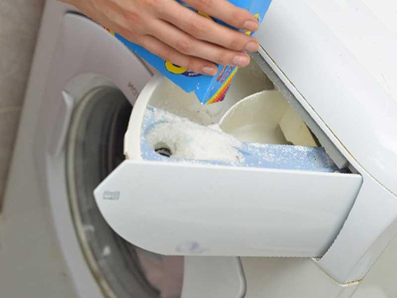 柔軟剤を洗濯機にいれる主婦さん