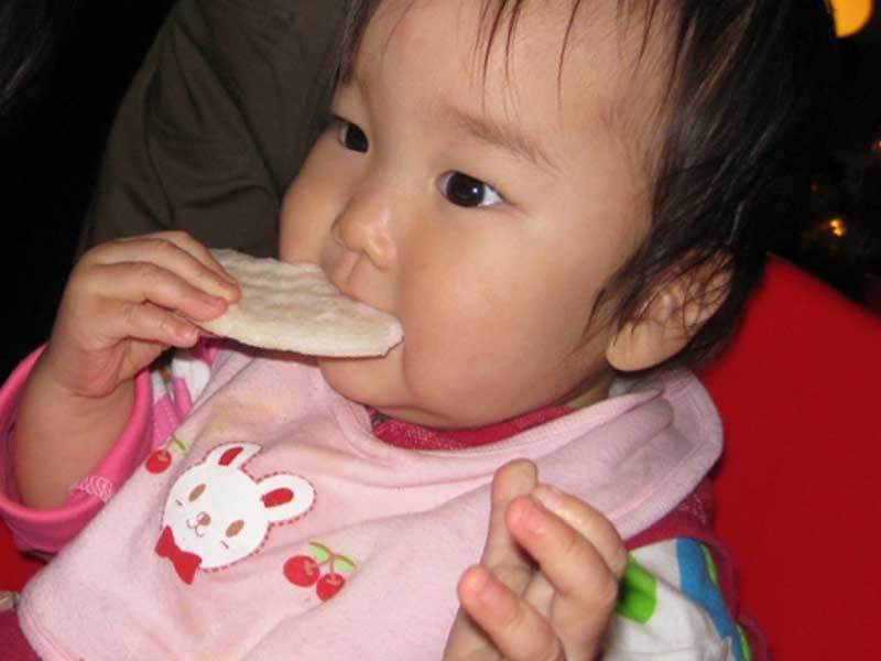 落ち着いておやつを食べる赤ちゃん