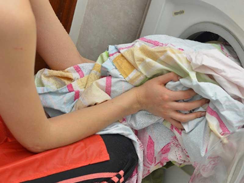 沢山の洗濯物を洗濯機の中に入れる女性