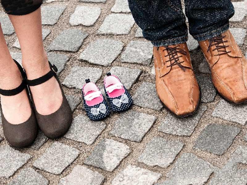夫婦の足の間に置いてある赤ちゃんの靴