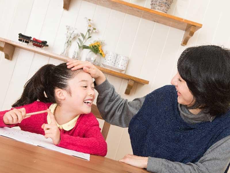勉強している子供の頭を撫でるお母さん
