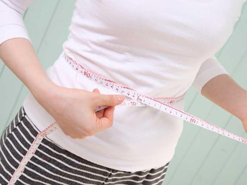 ダイエットしてウエストのサイズを測ってる女性