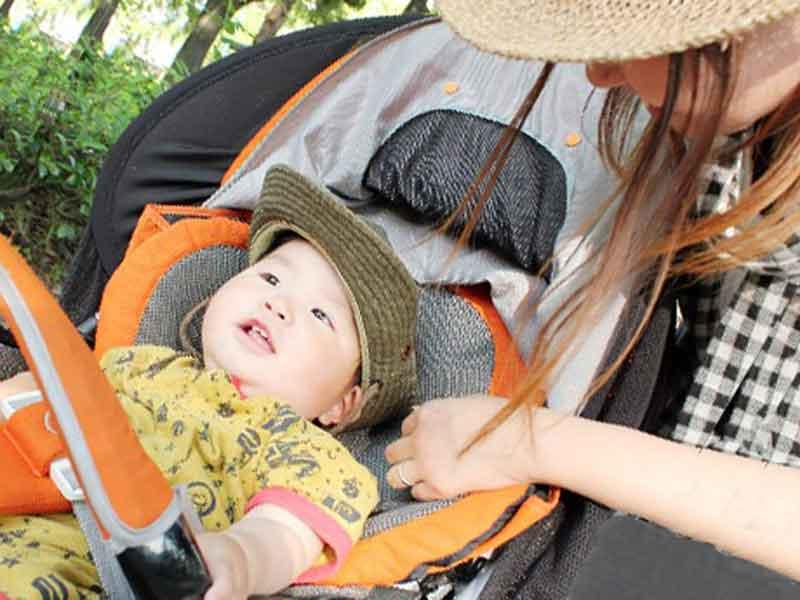 ベビーカーの中の赤ちゃんの様子をチェックしているお母さん