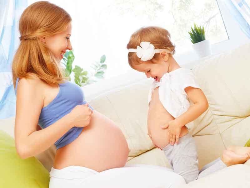 子供と遊んでいる妊娠中のお母さん