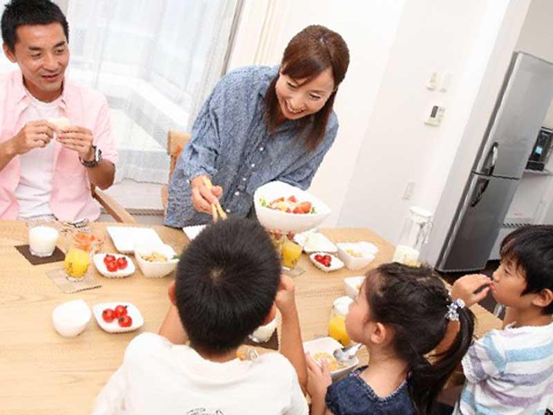 食卓を囲んで仲良く食事をする家族