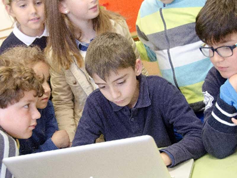 学校の授業でパソコンを使ってる小学生