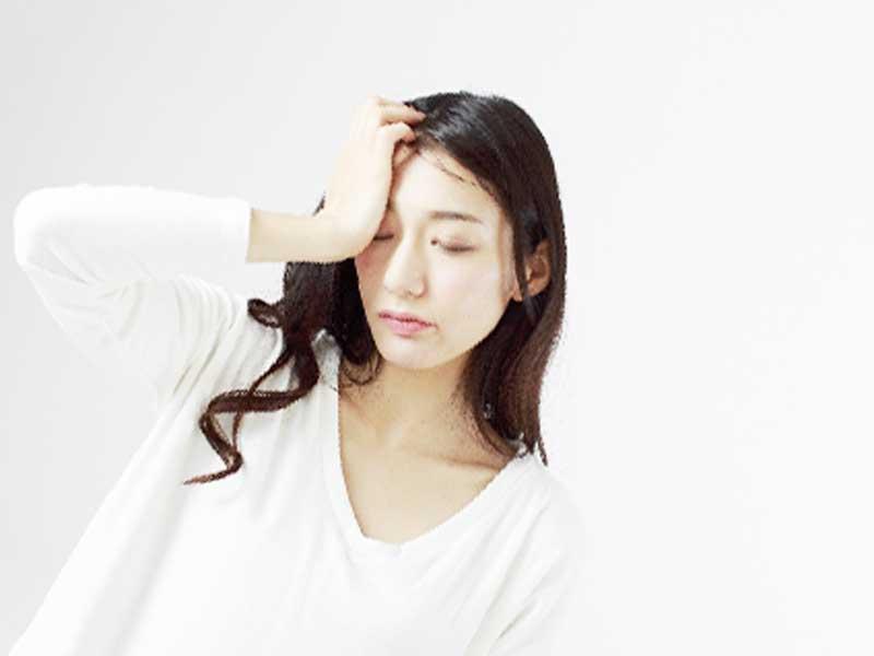 頭痛で頭をおさえてる女性