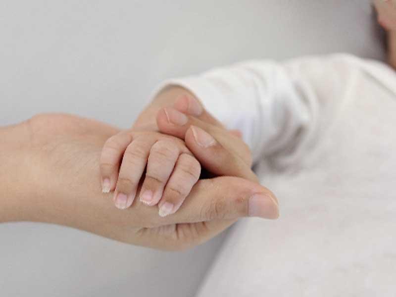 お母さんと手を繋いで寝ている子供