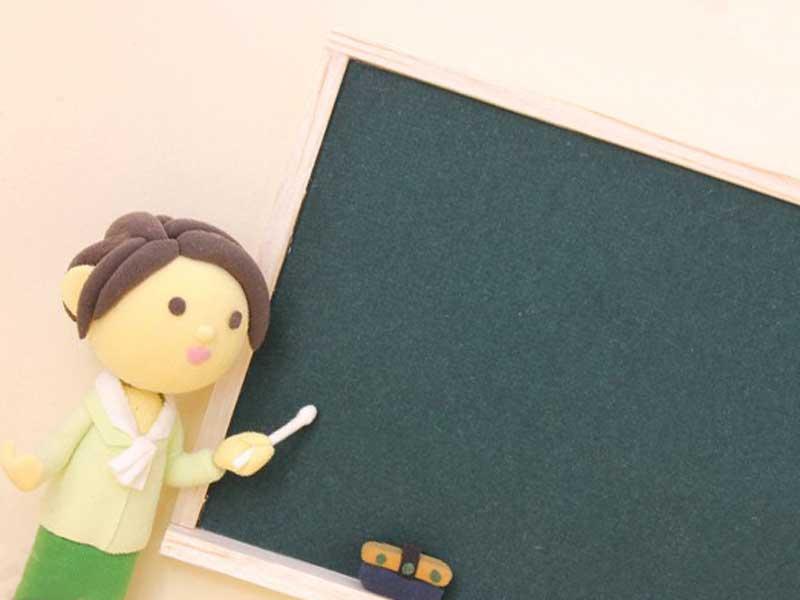 黒板の前に立つ女性のイラスト