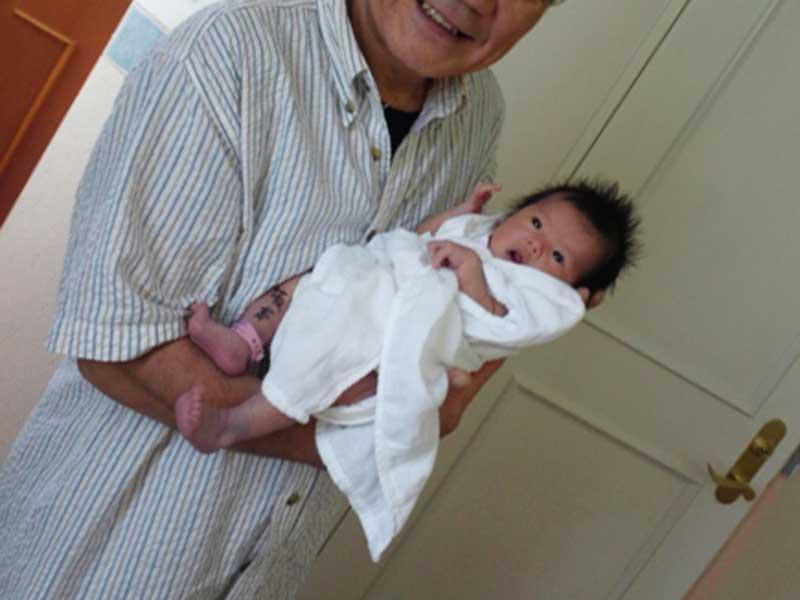 生まれたばかりの赤ちゃんを抱っこするおじいさん