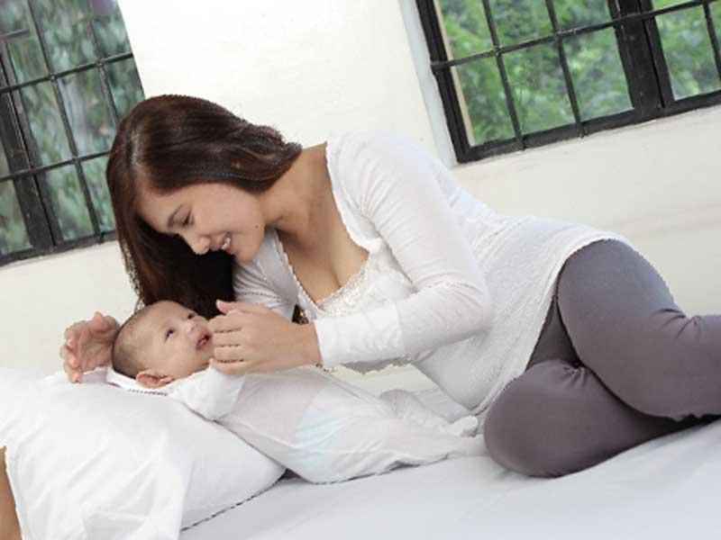 枕の上で横になっている赤ちゃんと遊ぶお母さん