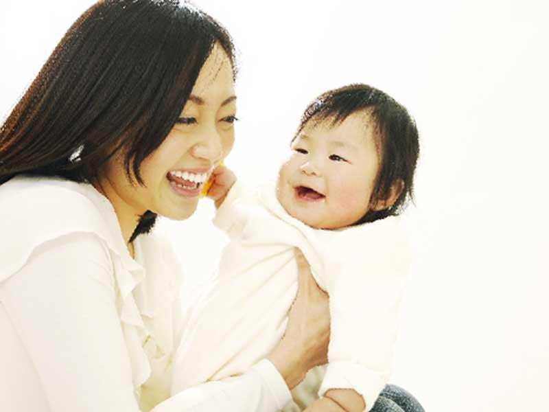 赤ちゃんとスキンシップをしているお母さん