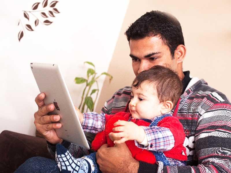 赤ちゃんを抱っこしてipadを一緒に見ているお父さん