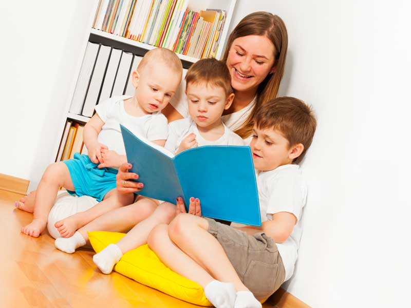 子供達に絵本を読んでいるお母さん