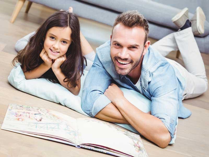 子供と楽しそうに絵本を読んでいるお父さん