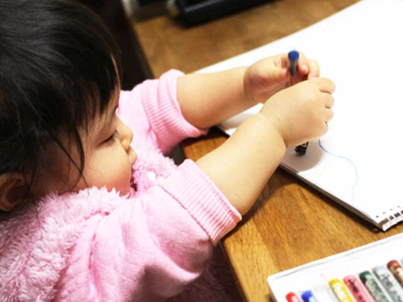 クレヨンで絵を描いてる子供