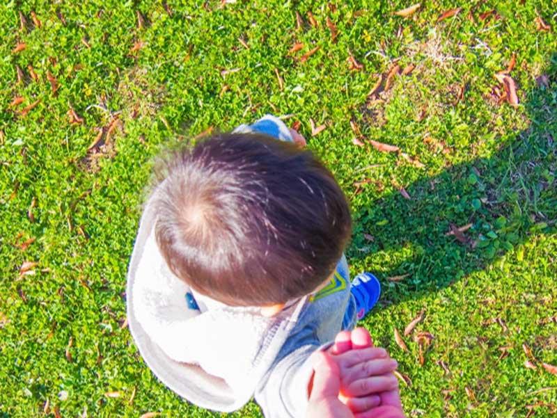 パパと手を繋いで散歩する赤ちゃん