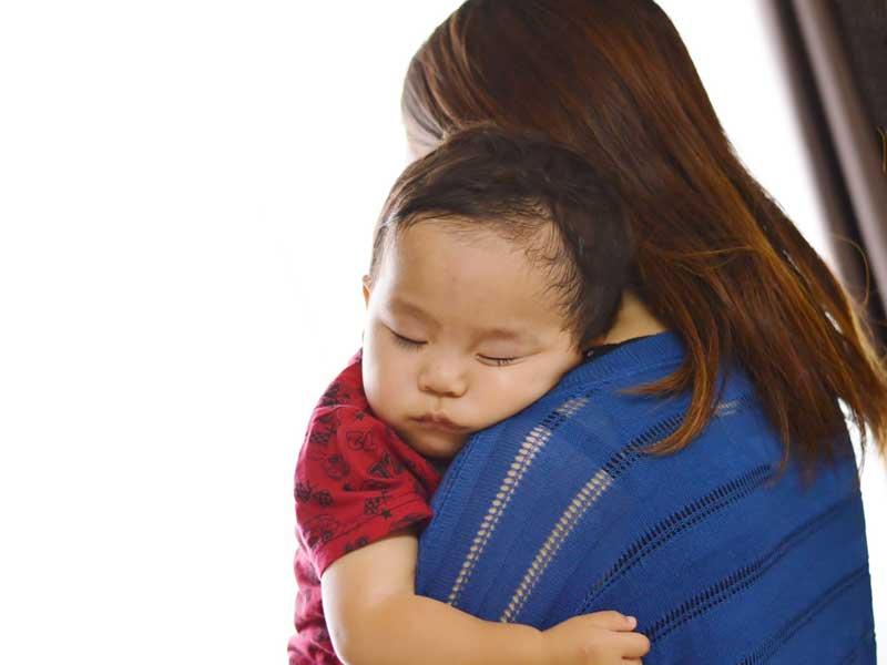 寝ている赤ちゃんを抱っこしているお母さん
