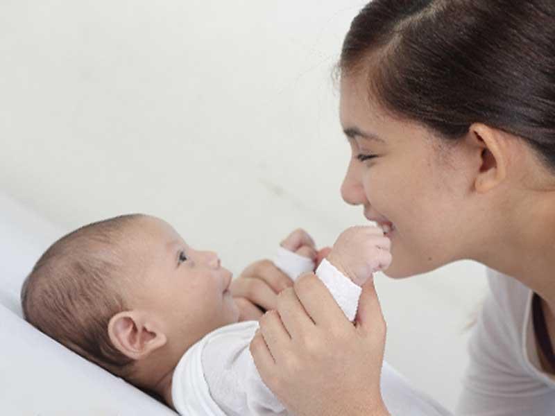 新生児を可愛がっているお母さん