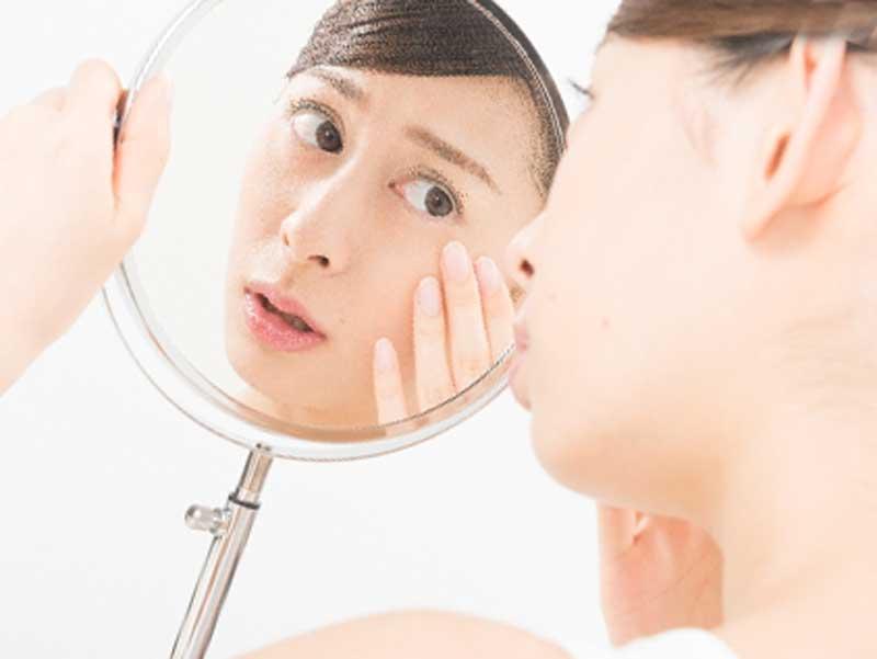鏡を見ながら顔のニキビを気にしている女性