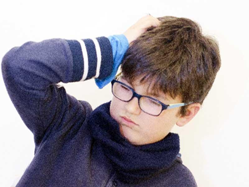 頭痛で頭をおさえている男の子