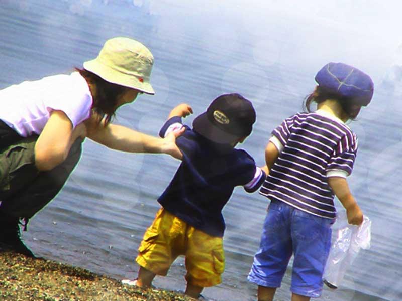 赤ちゃんと子供を連れて水遊びをしているお母さん