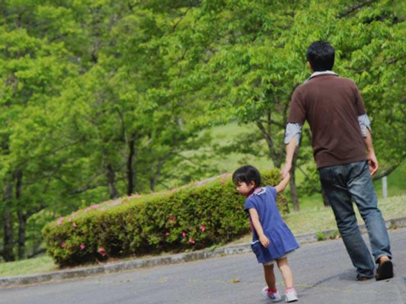 子供を連れて散歩するお父さん