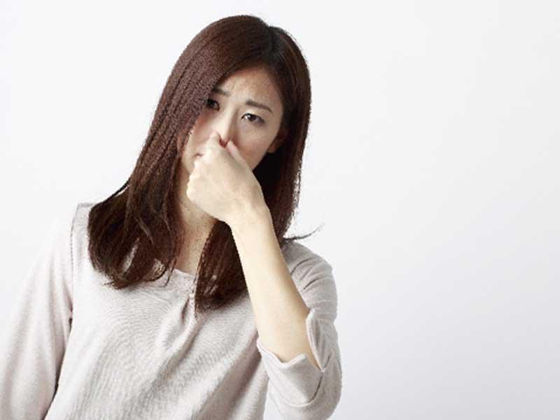 臭くて鼻をつまんでいる女性