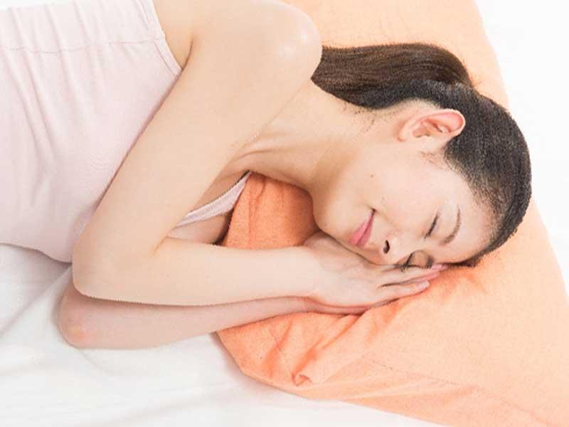 枕の上で気持よさそうに寝ている女性