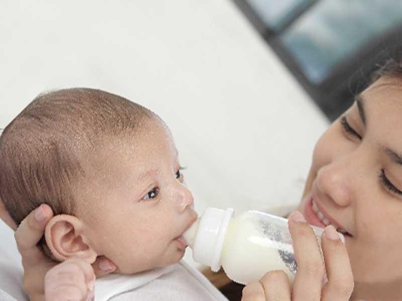 赤ちゃんにミルクを飲ませるお母さん